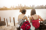 Rear view of female friends using phone while sitting at riverbank - CAVF00882
