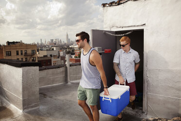 Male friends carrying cooler on building terrace - CAVF00903