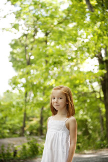 Portrait of smiling girl against trees in forest - CAVF00957