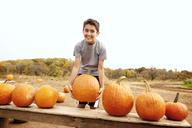 Portrait of smiling boy holding heavy pumpkin on field against clear sky - CAVF01004