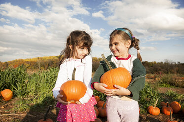 Happy girls holding pumpkins and looking face to face - CAVF01007