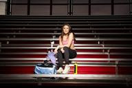 Portrait of beautiful sporty woman sitting in stadium - CAVF01013