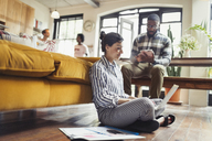 Female freelancer working at laptop on living room floor - CAIF04628
