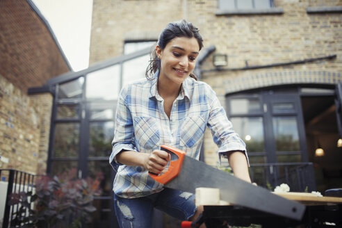 Young woman with saw cutting wood on patio - CAIF04676