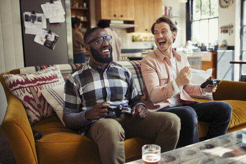 Laughing men friends playing video game on living room sofa - CAIF04700