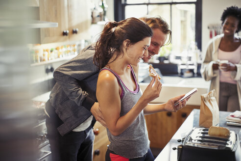 Smiling couple texting with smart phone, eating toast in kitchen - CAIF04703