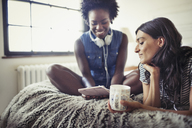 Women with headphones and coffee using digital tablet on bed - CAIF04724