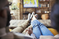 Affectionate couple holding hands, watching TV in living room - CAIF04736