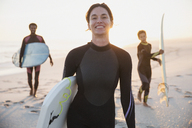 Portrait smiling female surfer in wet suit carrying surfboard with family on sunny summer beach - CAIF04781