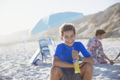Portrait smiling, confident boy drinking juice on summer sunny beach - CAIF04787