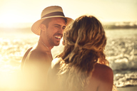 Laughing young couple on sunny summer beach - CAIF04796
