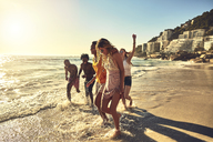 Playful young friends walking in sunny summer ocean surf - CAIF04799