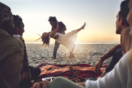 Playful young couple dancing on sunny summer beach - CAIF04811