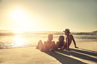 Young friends relaxing on idyllic, sunny summer sunset ocean beach - CAIF04814