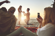 Young man proposing to woman on sunny summer beach with friends - CAIF04823