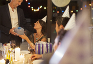 Man giving present at birthday party - CAIF04863