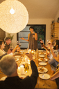 Woman giving toast at dinner party - CAIF04869