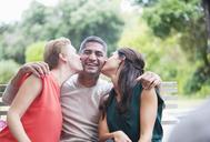 Women kissing man's cheeks outdoors - CAIF04896