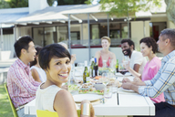 Woman smiling at table outdoors - CAIF04902