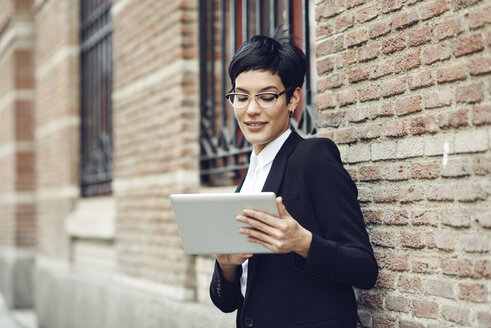 Portrait of content young businesswoman using tablet outdoors - JSMF00059