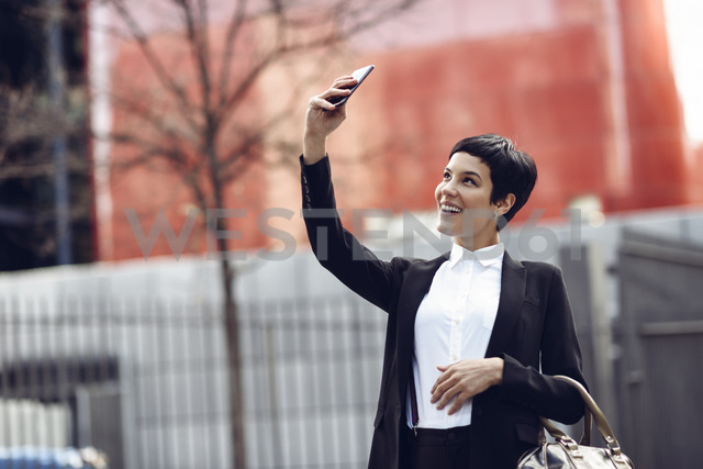 Portrait of smiling young businesswoman taking selfie with cell phone - JSMF00062