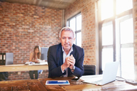 Portrait confident businessman with digital tablet and laptop working in office - CAIF04922