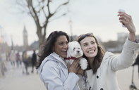 Playful, smiling lesbian couple with white dog taking selfie with camera phone in urban park, London, UK - CAIF04982