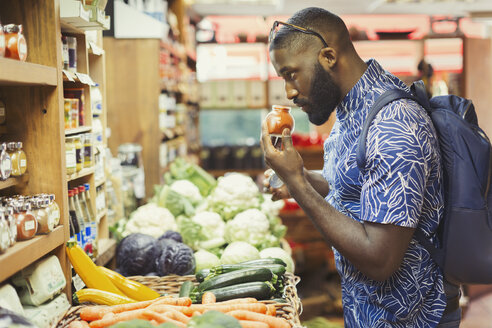Man shopping, smelling spices in grocery store - CAIF04994