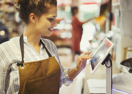 Female cashier using touch screen cash register in grocery store - CAIF05015