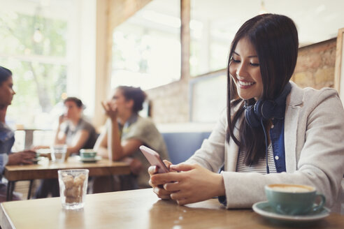 Smiling young woman with headphones texting with cell phone and drinking coffee at cafe table - CAIF05021