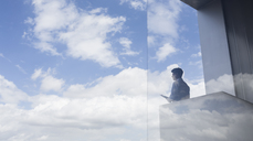 Pensive businessman standing on modern balcony looking at blue sky and clouds - CAIF05030