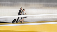 Businessman and businesswoman with suitcase running up airport ramp - CAIF05036
