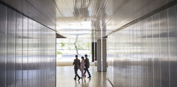 Business people walking in modern office corridor - CAIF05042
