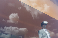 Businessman using virtual reality simulator glasses at window with reflection of clouds - CAIF05051