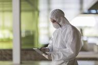 Scientist in clean suit using digital tablet - CAIF05054