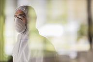 Pensive scientist in clean suit looking away - CAIF05069