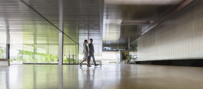 Businessman and businesswoman walking in modern office lobby - CAIF05075