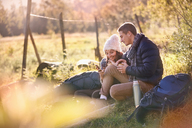 Young couple hikers resting in sunny grass using cell phone and digital tablet - CAIF05081