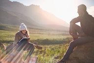 Young couple hiking, resting and writing in sunny remote field - CAIF05096