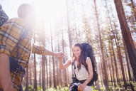 Young man helping girlfriend with backpack hiking in sunny woods - CAIF05102