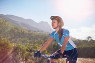 Young woman mountain biking in sunny landscape - CAIF05108