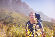 Young man with backpack hiking in sunny valley - CAIF05111