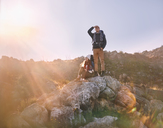 Young couple hiking, standing on rock - CAIF05117