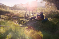 Young couple with backpacks hiking, resting in sunny remote field - CAIF05123