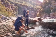 Young couple with backpacks hiking, splashing water at stream - CAIF05129