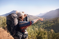Young couple hiking, looking at sunny view with binoculars - CAIF05132