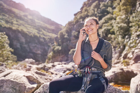 Young woman talking on cell phone below sunny, craggy cliffs - CAIF05144