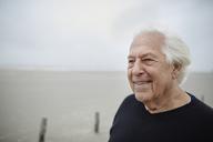Smiling senior man looking away on beach - CAIF05168