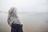 Senior woman with hand in long gray hair on winter beach - CAIF05171
