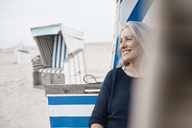 Smiling senior woman looking away on beach - CAIF05180